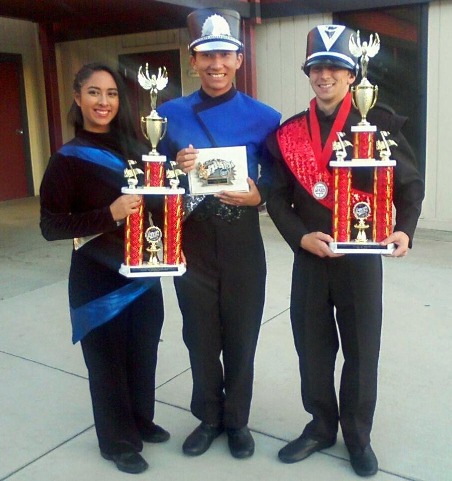 Color Guard Captain Genesis Johnson, Drumline Captain Victor Pham, Drum Major Matthew Marquez posing with awards at Championships.