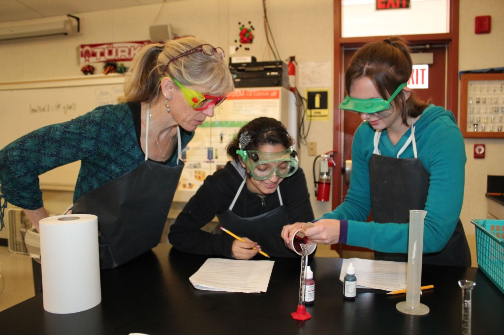 Chemistry teacher Ms. Rachel Kanowsky oversees an experiment being conducted by Cristal Vasquez (middle) and Olesiya Driga (2012).