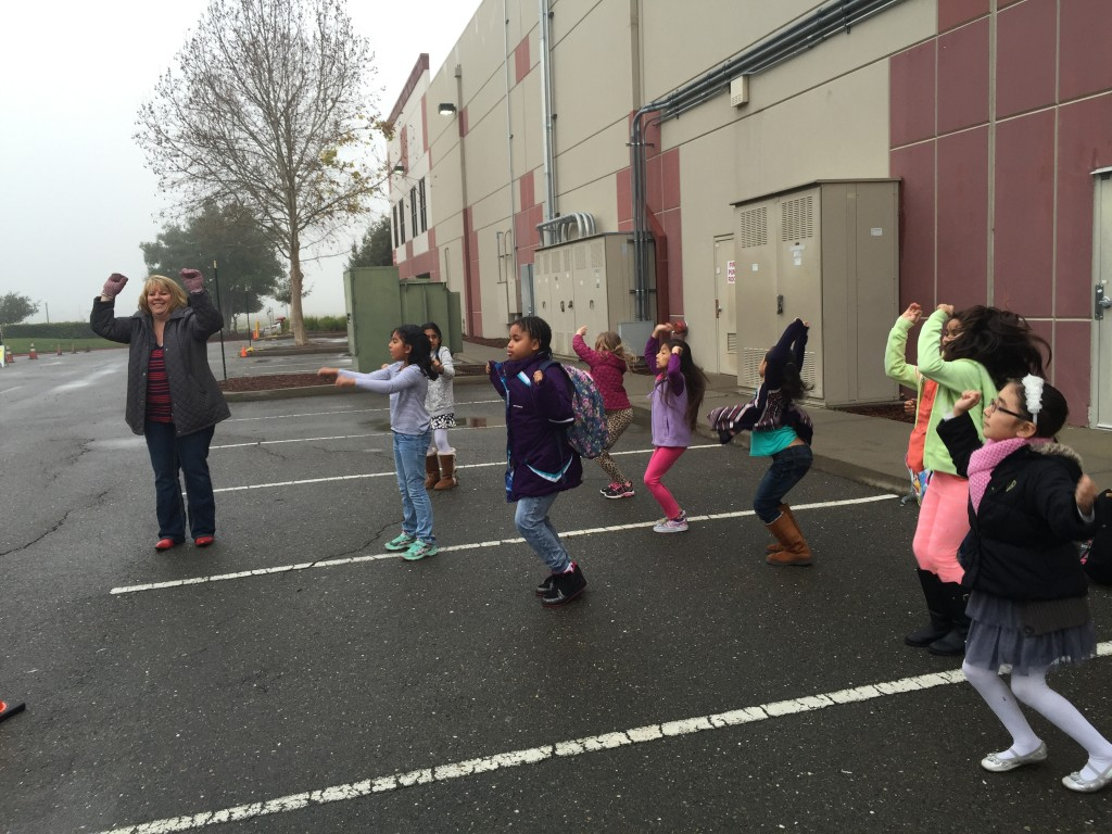 Principal Jennifer Kloczko gets her groove on with Star Academy students every morning in the car loop. / Photo: J. Mock