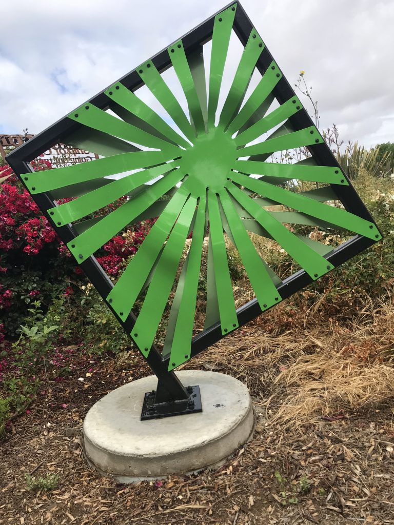 Image of bright green sunburst metal sculpture mounted on a square frame.