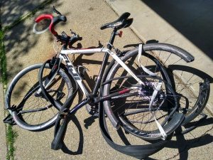 Image of bicycle with bent and broken wheel frames and tires.