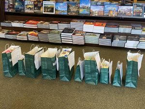 Image of several paper bags of varying sizes in a row that contain books, puzzles and more.