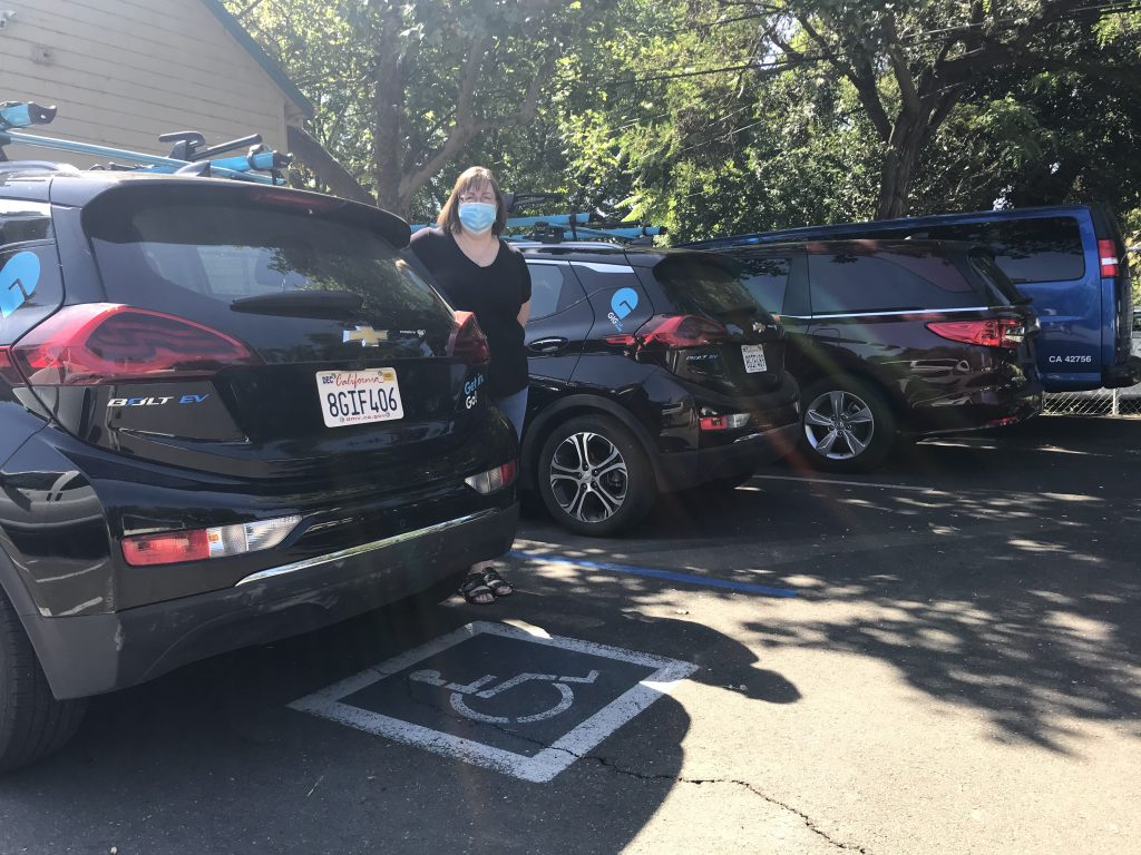 Image of four black cars parked in a row. The first two have the bright blue GIG logo.