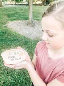 "Child holding rock with words ""better times are near"" painted on it."
