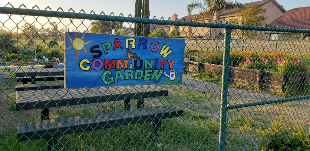 Image of colorful hand-painted sign which reads Sparrow Community Garden.