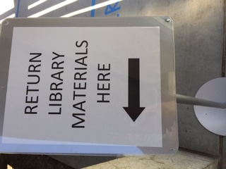 "Image of sign which reads ""Return Library Materials Here."""