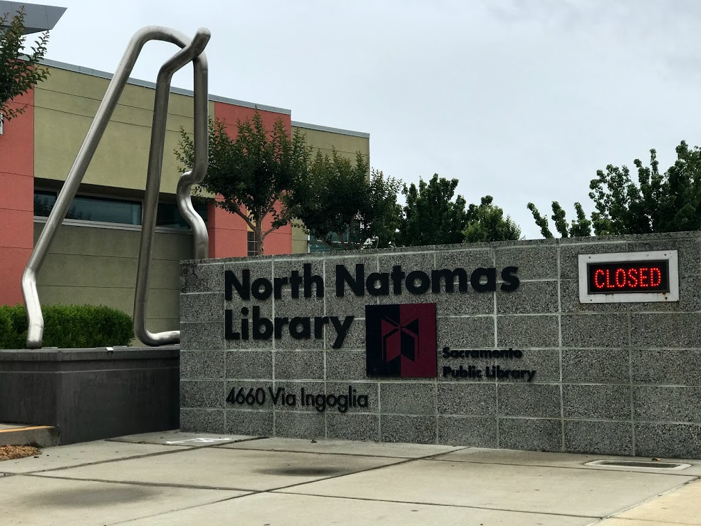 "Image of North Natomas Library branch sign with the word ""closed"" in red."