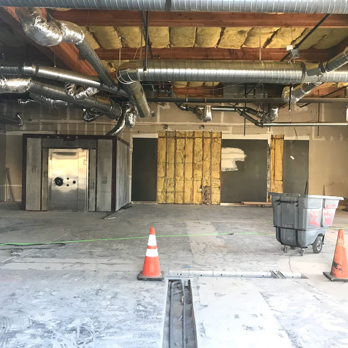 Image of duct work, concrete floor and orange caution cones. The door to the vault is visible.