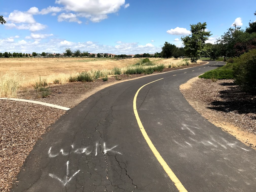 "Image of paved, two-lane bike trail where the word ""walk"" has been written in chalk or spray painted with an arrow."
