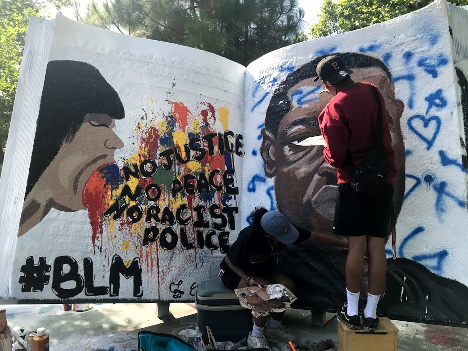 """Image of large book. Painted on the left is a person with multiple colors of paint spilling out of their mouth and the words """"No Justice No Peace No Racist Police"""" and painted on the right is a portrait of George Floyd who was killed while in police custody in Minnesota."""