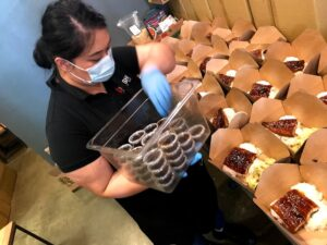Image of woman wearing face mask and gloves placing small containers of sauce into a boxed meal.