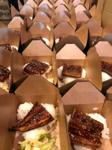 Close up image of boxed meal with white rice and piece of grilled eel.