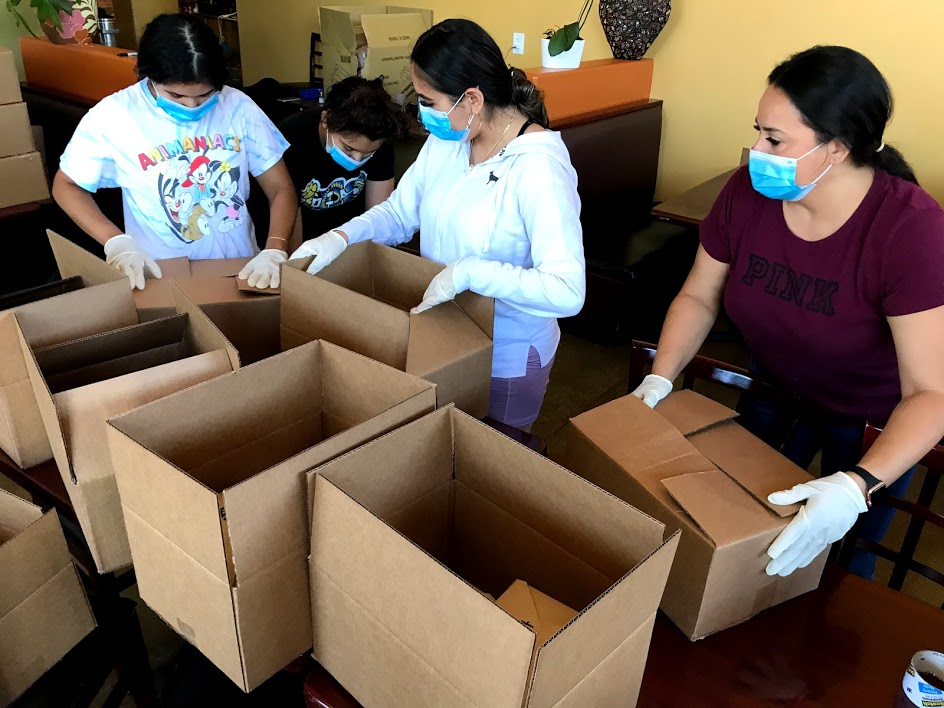 Image of four women in the process of packing and closing cardboard boxes which hold box meals.