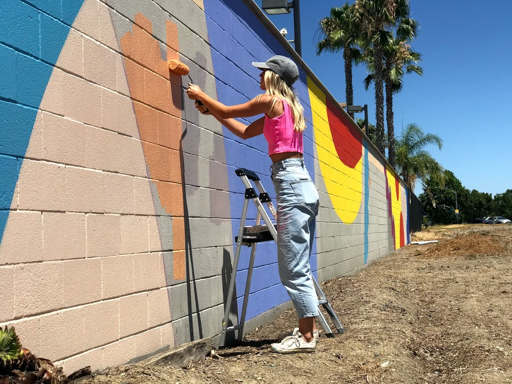Image of woman painting a peach color on wall.