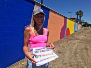 Image of woman holding rendering standing in front of wall painted colorfully.