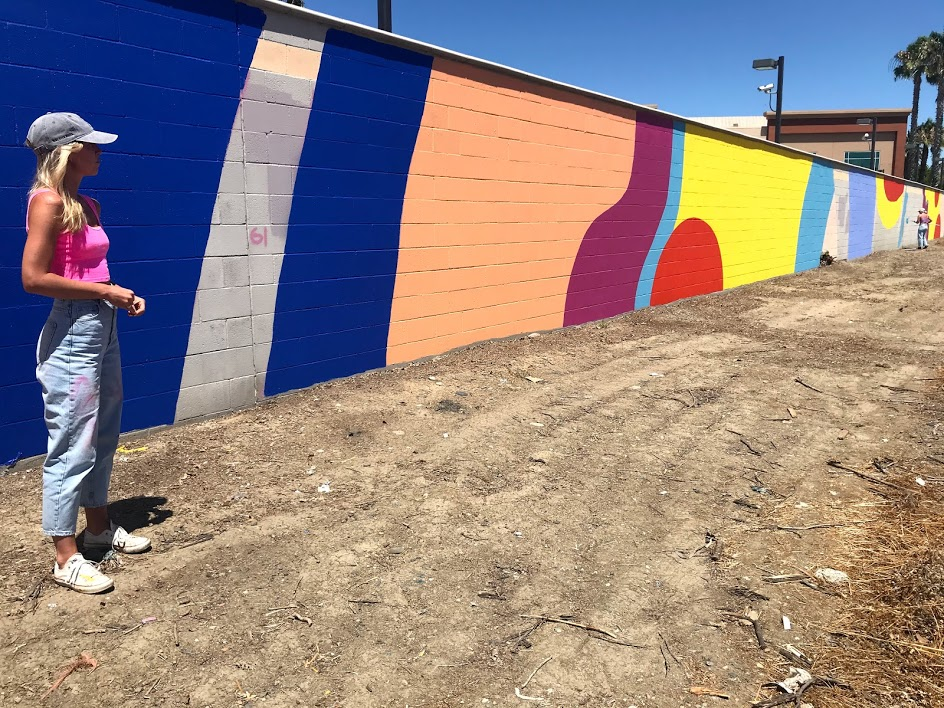 Image of woman standing in front of wall painted bright colors. A second person is painting in the distance.