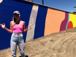 Image of woman standing in front of painted walls hands outstretched.