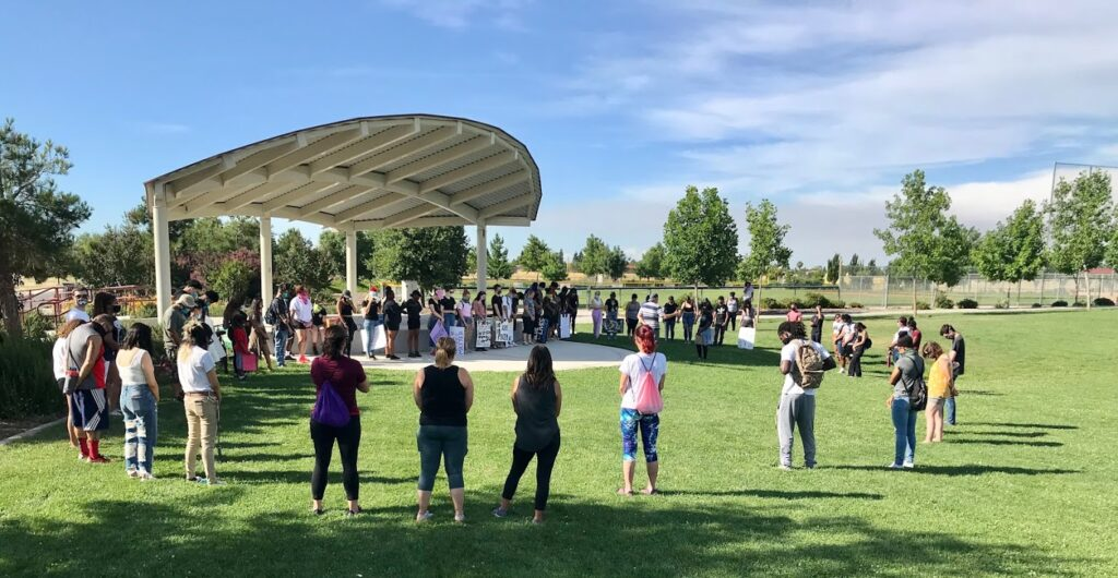 Image of about five dozen protesters standing in a large circle within an amphitheater.