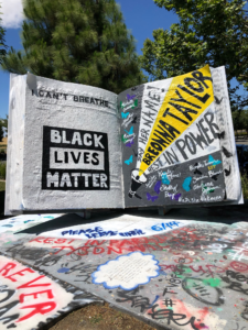"Image of large book painted with the words ""Black Lives Matter"" and the names of Black men and women who have died in police custody."