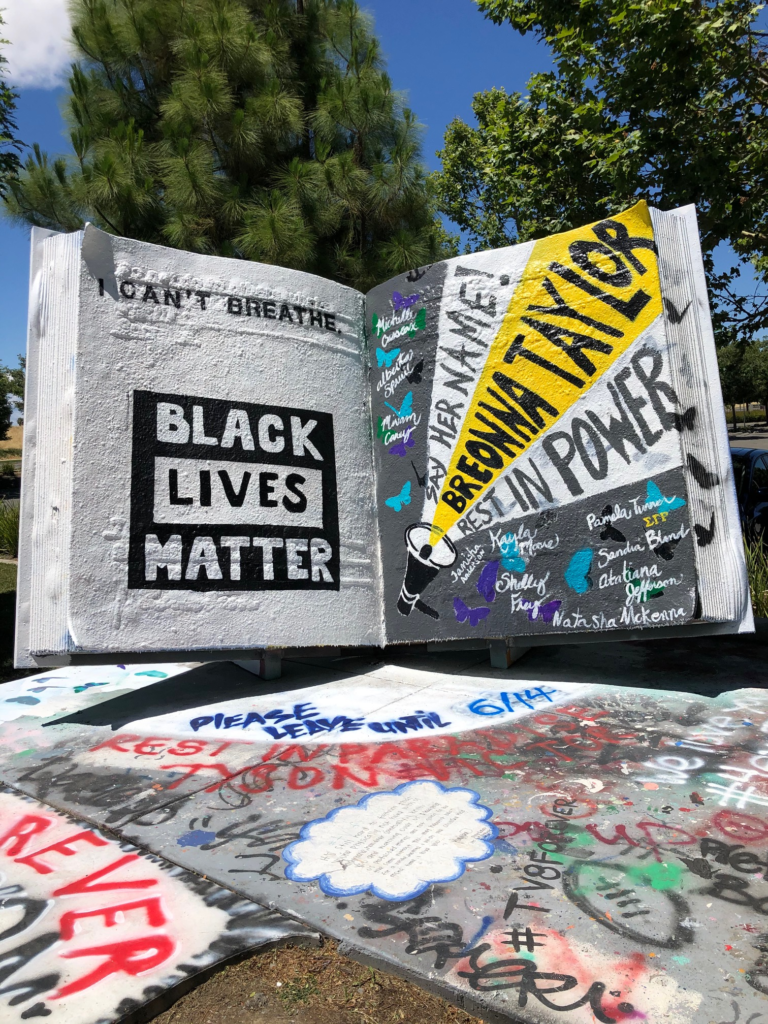 """Image of large book painted with the words """"Black Lives Matter"""" and the names of Black men and women who have died in police custody."""