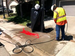 Image of man holding power washer hosing off sidewalk.