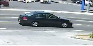 Image is side view of a dark-colored four-door sedan.