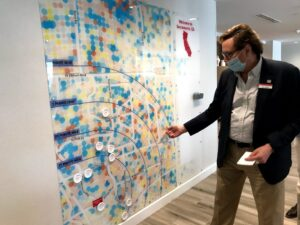 Image of man pointing to wall sized map.