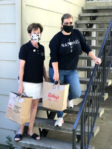 Image of Heick and Ashby standing together each holding a bag of grocers.