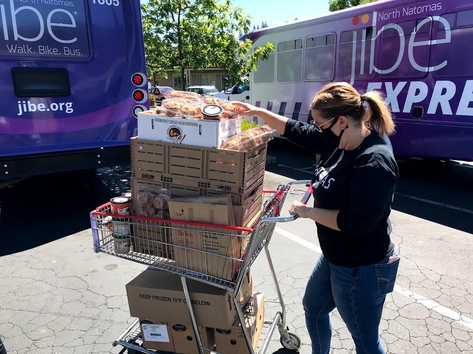 Image of Ashby pushing shopping cart full of food.
