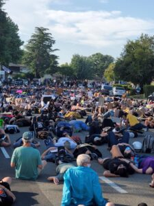Image of hundreds of people lying down on the street.