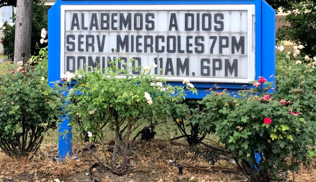 "Image of sign which reads ""Alabemos A Dios Serv Miercoles 7pm Domingo 8am 6pm."