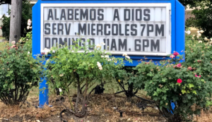 """Image of sign which reads """"Alabemos A Dios Serv Miercoles 7pm Domingo 8am 6pm."""