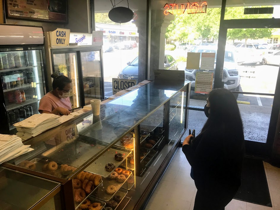 Image of two people. One woman is getting donuts from the pastry case while the other waits.