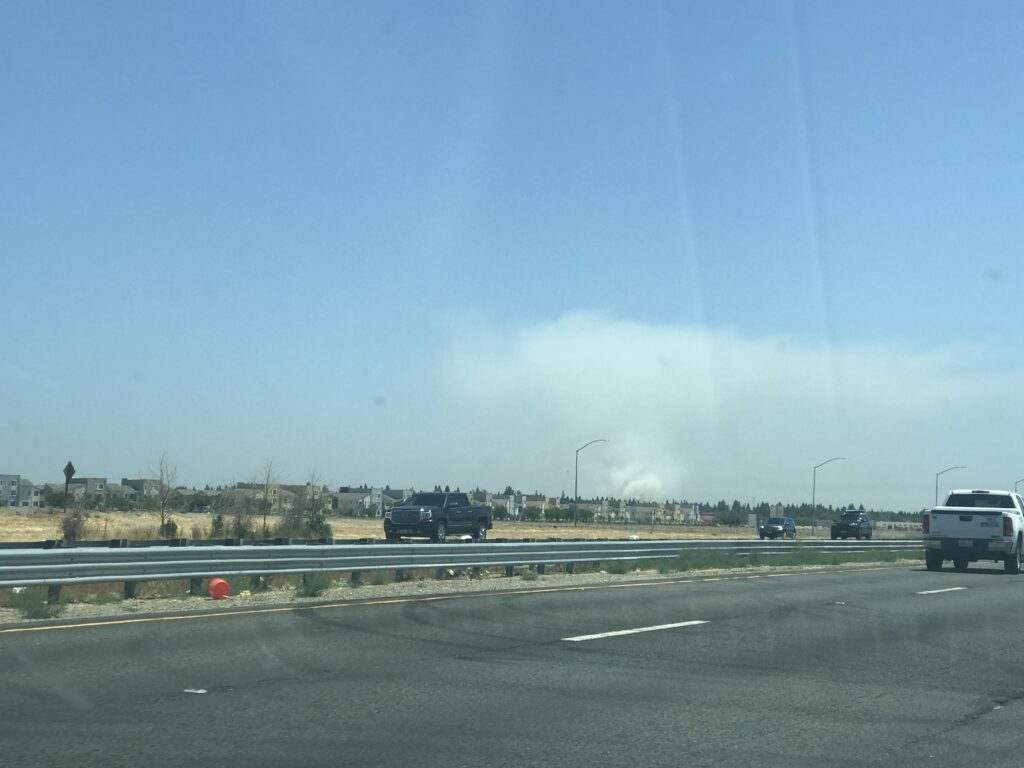 Image of freeway in foreground and plume of smoke in distance.