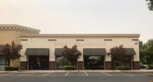 Image of former Men's Wearhouse building in Natomas. An outline of the store's name is visible on the building.