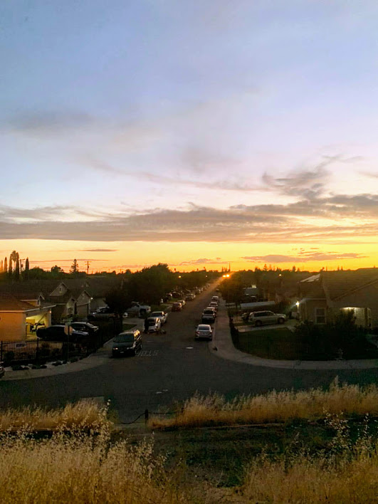 Image of neighborhood street with sunset in the distance. Appears to be taken from a higher elevation.
