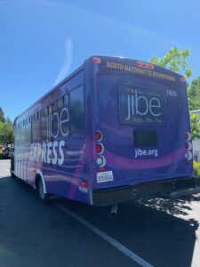 Image of side view of purple Jibe Express shuttle bus.