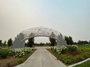Image of an arch over a path. The arch is made of hundreds of interwoven sculpted baseball bats.