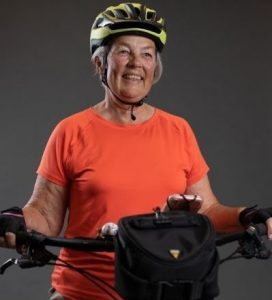 Image of older woman wearing orange shirt and bike helmet standing at bike handlebars.