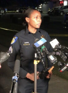 Image of police officer standing in front of several TV microphones.