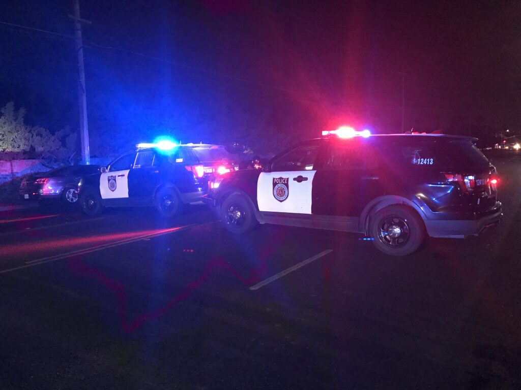 Image of two police cars in the dark with flashing red and blue lights.