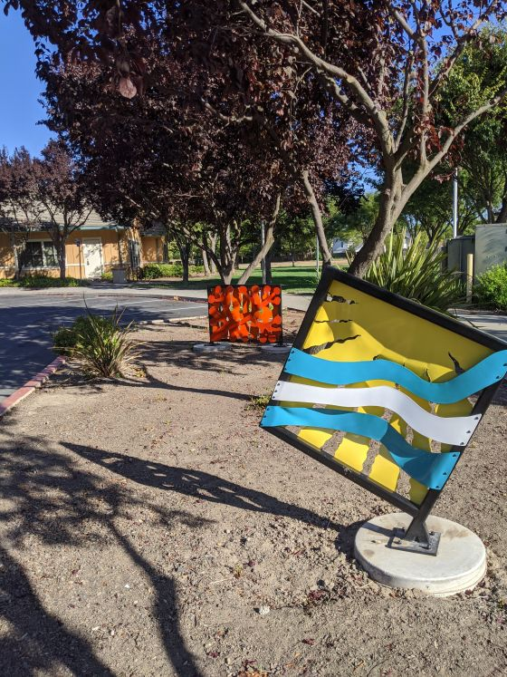 Image of metal sculptures, square in shape and multicolored.