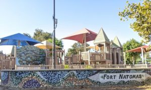 """Image of playground with words """"Fort Natomas"""" on a tile wall."""