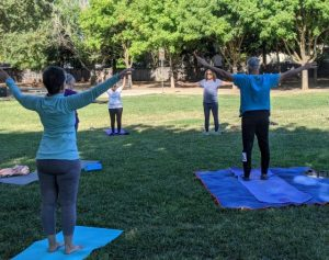 Image of people standing on yoga mats on the grass with arms stretched up and outward.