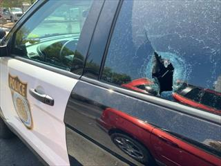Image of police vehicle with bullet hole and broken window.