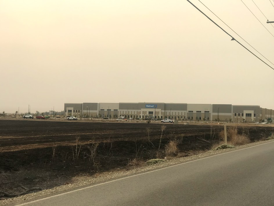 Image of blackened field in foreground and Walmart warehouse in background.