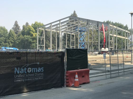 Image of construction site with Natomas Unified School District banner on fence in the foreground.
