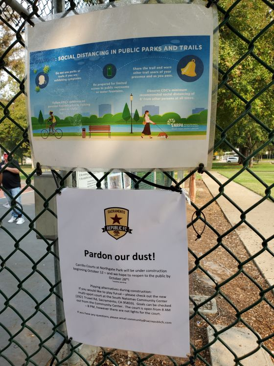 Image of sign on fence reminding park goers about social distance guidelines with a note about the futsal court expansion and target reopening date of Oct. 28.