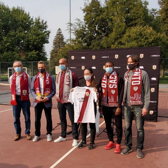 Image of several people posing for a group photo. One woman, at the center, is holding up a Sacramento Republic FC shirt.