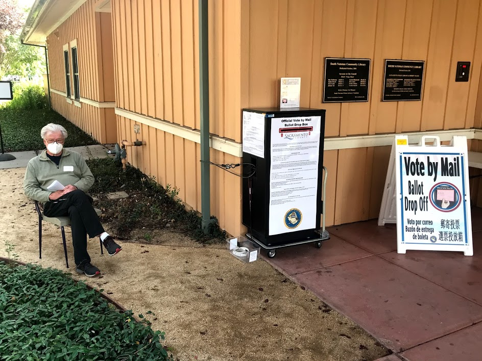 Image of man wearing a mask sitting in chair adjacent to ballot drop box.